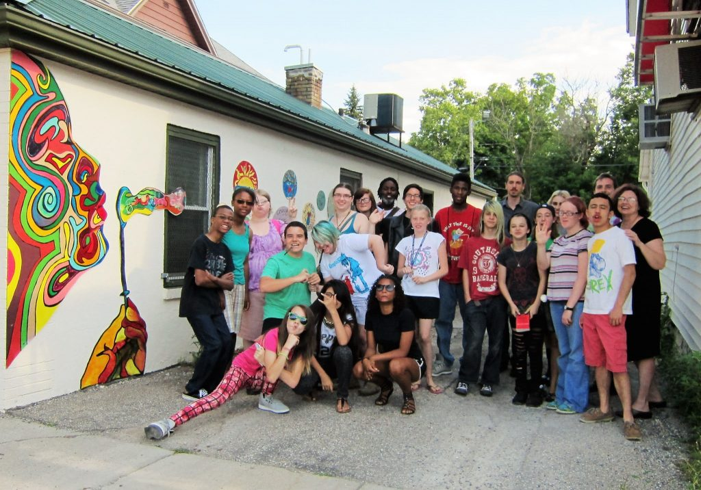 Participants in Teen Open Studio and Guest Artist Mathew Smith pose by the mural they designed and painted at Lansing's Women's Center, 2014.